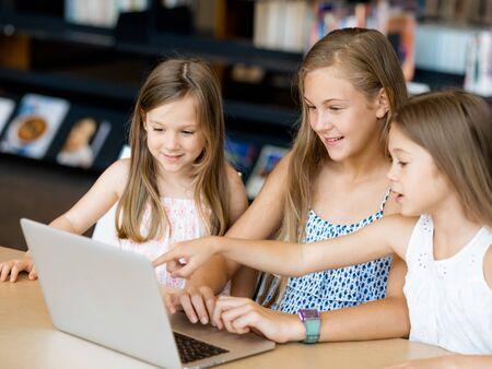 ni�as peque�as: Ni�as con un ordenador port�til en la biblioteca
