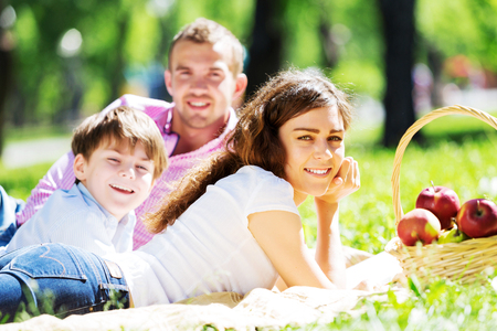 young feet: Happy family having weekend in summer park