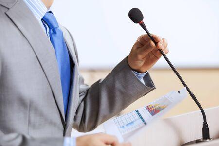 reporte: Empresario de pie en el escenario y la presentaci�n de informes para la audiencia