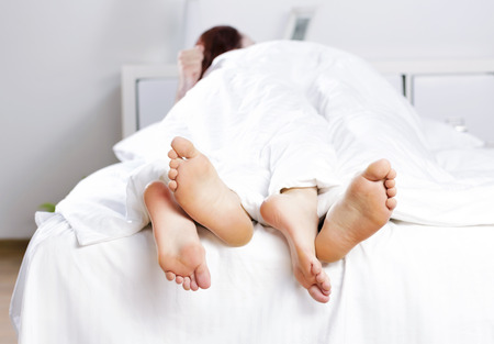 pareja en la cama: Cerca de cuatro pies en una cama Foto de archivo