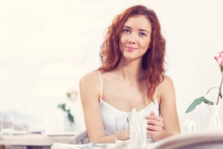 red haired woman: Young pretty red haired woman sitting in cafe