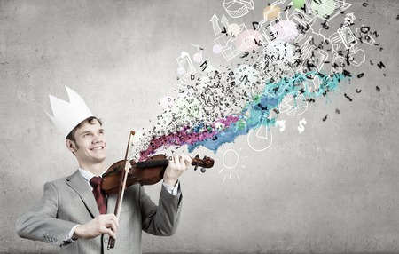 virtuoso: Young handsome businessman wearing white paper crown and playing violin