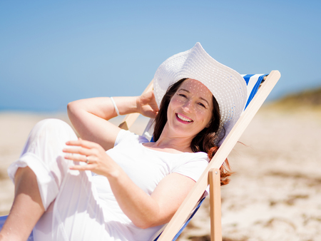beautiful mature woman: Woman in white clothes on the beach on sunny day
