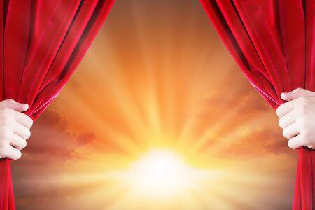 赤いカーテンを開き手のクローズ アップ。テキストのための場所