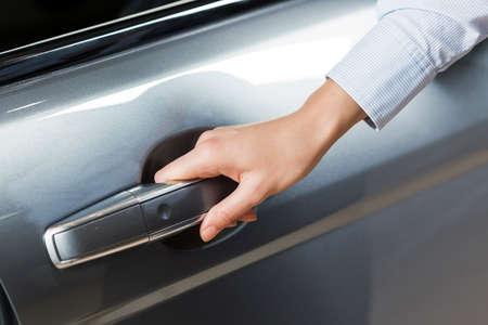 Close up of human hand opening door of car Stock Photo
