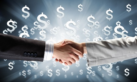 technology deal: Close up of business handshake on digital