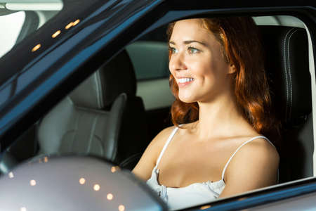 auto leasing: Young pretty woman in car salon sitting in car