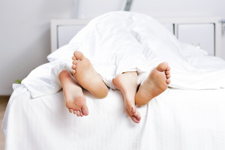 pareja durmiendo: Cerca de cuatro pies en una cama Foto de archivo