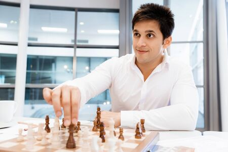 firmness: Two businessmen with chess in office