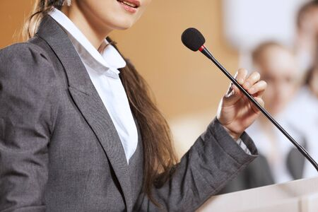 spokesman: Businesswoman standing on stage and reporting for audience Stock Photo