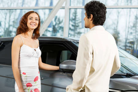 Young man dealer in auto salon presenting car to customer Stock Photo