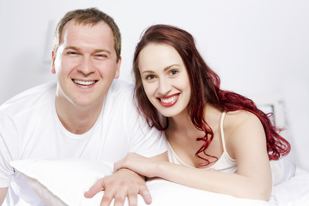 couple talking: Young couple talking while lying in bed in the morning Stock Photo