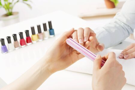 manicure salon: Woman in nail salon receiving manicure by beautician Stock Photo