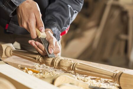 Close up of carpenters hands working with cutter in his studio