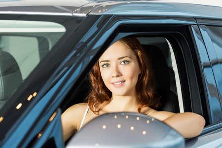 car loans: Young pretty woman in car salon sitting in car