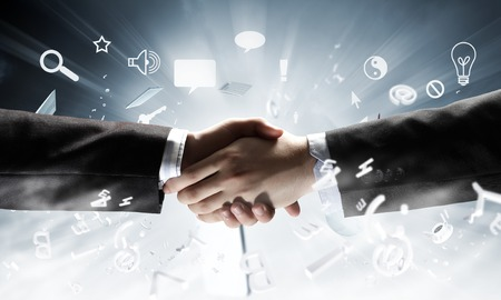 technology agreement: Close up of business handshake on digital