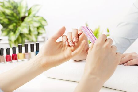 hand: Woman in nail salon receiving manicure by beautician Stock Photo
