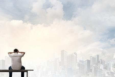 Hombre gordo sentado en el banco con la espalda y mirando de lejos