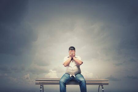 gordos: Hombre gordo sentado en el banco de cerrar los ojos con las manos