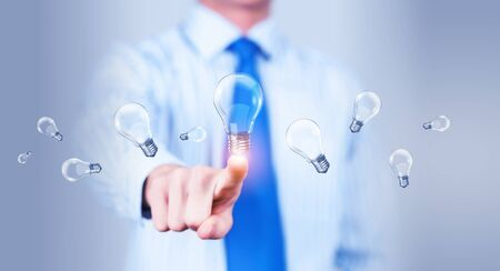 innovator: Close up of businessman touching with finger virtual light bulb Stock Photo