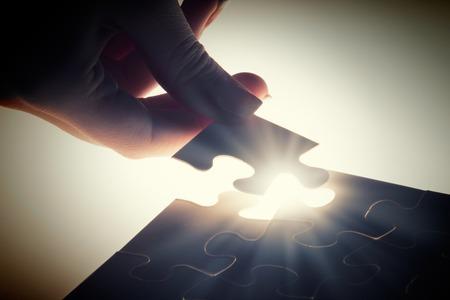 Nahaufnahme der Hände Verbindungspuzzleelement und macht Puzzle komplett Standard-Bild