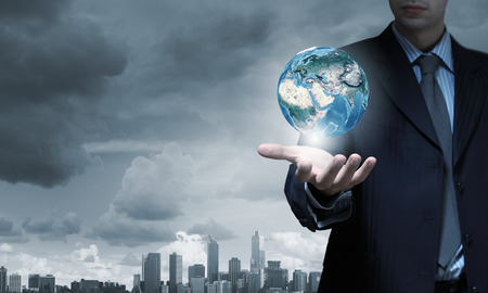 Hand of businessman holding earth planet. Elements of this image are furnished by NASA