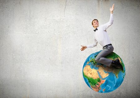 supremacy: Young businessman riding Earth planet. Elements of this image are furnished by NASA