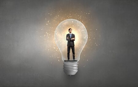 man in suite: Man in business suite stay inside light bulb Stock Photo