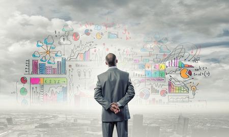 ビジネス マーケティング戦略を見て実業家の背面図