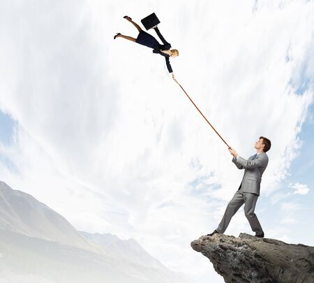 lead rope: Young man on lead of colleague trying to escape Stock Photo