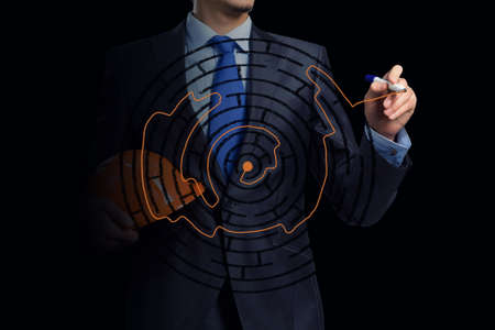 drawing a plan: Close up of businessman drawing way out of labyrinth Stock Photo