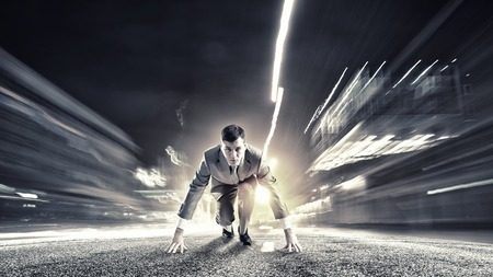 business men: Young determined businessman standing in start position