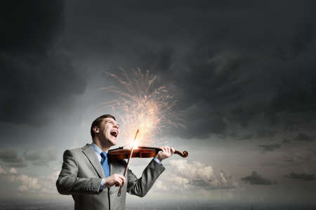 virtuoso: Young emotional businessman playing with passion violin instrument