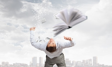 bent over: Businessman bent over and evading from book Stock Photo
