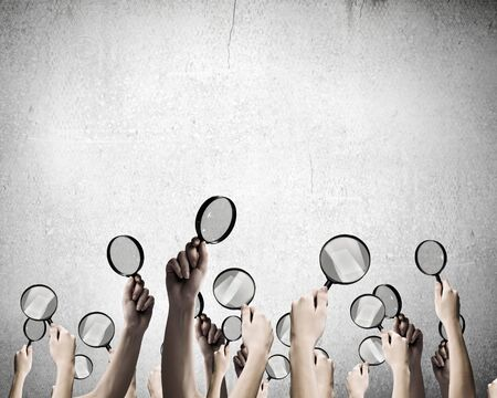 close p: Close p of mans hands holding magnifying glass