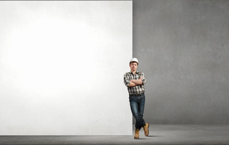 Young builder man leaning on white blank banner. Place for text