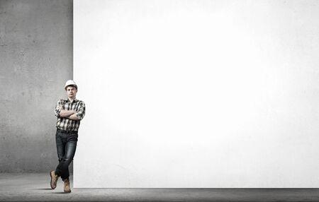 builder: Hombre constructor joven, apoyado en la bandera en blanco blanco. Lugar para el texto Foto de archivo