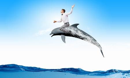 dolphin: Jeune homme gai saut circonscription de dauphin d'eau Banque d'images