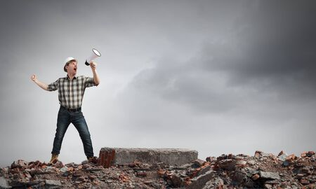 emotionally: Young man engineer screaming emotionally in megaphone Stock Photo