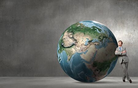 entrepreneur: Businessman leaning on huge Earth planet. Elements of this image are furnished by NASA
