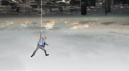 hardship: Young businessman hanging on rope above city Stock Photo