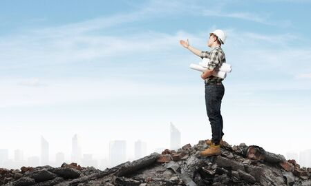 construction project: Young man builder looking thoughtfully at construction project. Idea concept Stock Photo