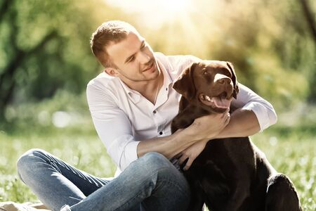 cute guy: Young guy with retriever on walk in summer park Stock Photo