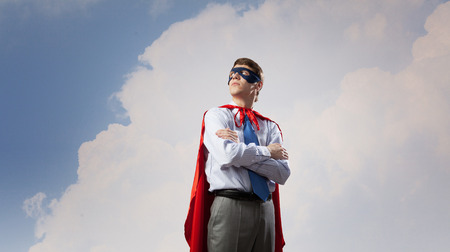 Young man in superhero costume representing creativity concept