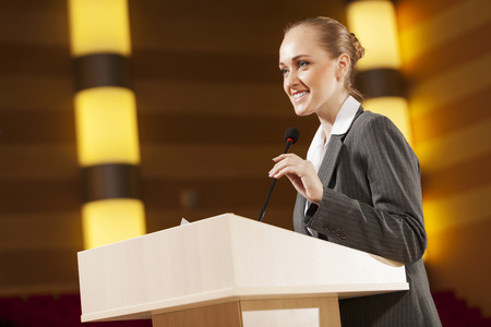 Businesswoman standing on stage and reporting for audience Imagens