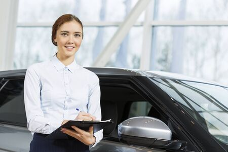 auto leasing: Young pretty woman dealer in showroom standing near car