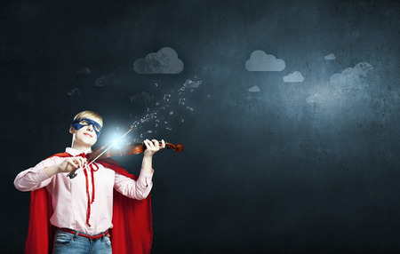 powerful creativity: Young woman in super hero costume playing violin