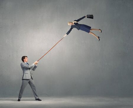 office slave: Young man on lead of colleague trying to escape Stock Photo