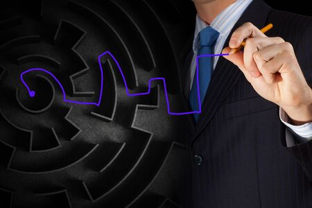 way out: Close up of businessman drawing way out of labyrinth Stock Photo