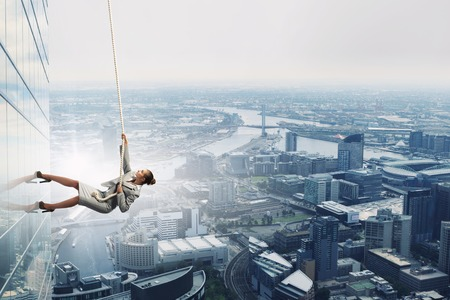 Concept of competition with businesswoman climbing office building with rope